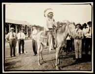 Unidentified group behind Native American man on horse