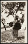 Unidentified Native American woman carrying wood