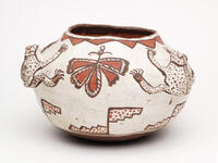 Polychrome ceramic frog effigy jar with black, brown, and red designs on a white background