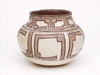 Polychrome ceramic jar with black/brown and red geometric designs on a white background