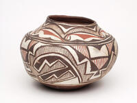 Ceramic polychrome jar with black/brown and red geometric designs on a white background