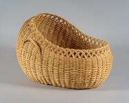 Oval shaped double walled buckbrush basket crib with handles
