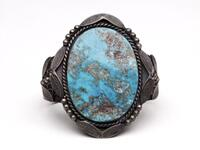 Large silver cuff bracelet with stamped designs and large turquoise inset