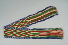 Finger woven sash with fringe and red, white, green, and royal blue border with white beading and an arrow design