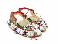Beaded leather moccasins with white beaded border around perimeter with tipi designs