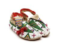 Beaded buffalo hide moccasins with metal cone tassels on the tongue