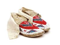 Beaded leather moccasins with white beaded border around perimeter with geometric designs and cloth cuffs