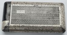 Silver cigarette case with embossed designs on front and back