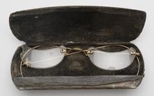 Black metal case with velvet lining containing gold eyeglasses with half-moon-shaped lenses and metal ear pieces