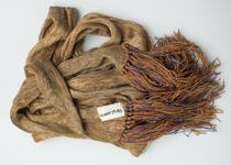 A long, thin scarf with mixtures of tan and brown colors and hints of light blue
