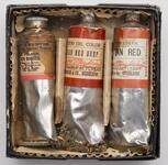 Three paint tubes in a small cardboard and metal container
