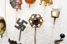Long gold pin with a flower-like design and a purple stone center