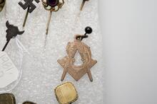 Brass colored charm of Mason's symbol