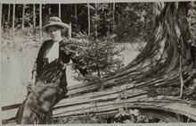 Nancy C. Russell seated on a fallen tree