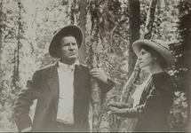 Photograph of Charles M. Russell and Nancy C. Russell posing in the forest near a tree