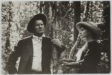 Charles M. Russell and Nancy C. Russell posing near a tree in the forest