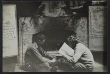 Two men seated in front of fireplace