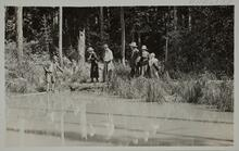 Charles M. Russell and Nancy C. Russell standing with friends near still water line on the bank