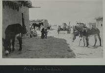 Photograph of two young children near an adobe house