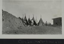 Three people near a group of tipis on the prairie