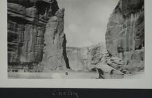 Photograph of cliffs near Canyon de Chelly and small figures near bottom center of image