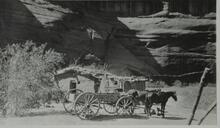 Horse-drawn wagon sitting in front of small adobe structure in a Canyon de Chelly