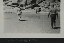 Four people walking near cliffs in canyon