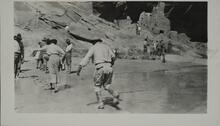 Large group of people near set of ruins in canyon wall