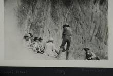 Group of people seated or standing in canyon