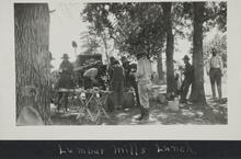 Large group of people under trees gathered around a wagon and tables with food