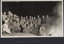 Large group of men and women sitting and standing around a bonfire