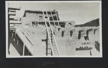 Photograph of an adobe house with ladder leading to the roof