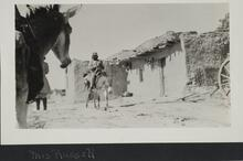 Two people on burros near other people standing next to adobe buildings