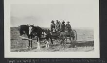 Five or six men sitting on a wagon drawn by two horses