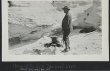 Howard Eaton standing near a campfire