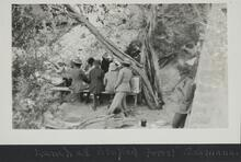 Group of people sitting at a picnic table eating