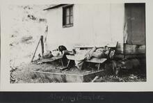 Photograph of two people sleeping on benches near a small building outdoors