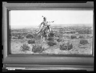 Negative of a painting of an Indian man on horseback on the plains