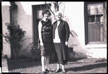Two Women Standing by House