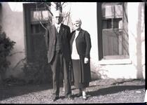 Man and Woman Standing by House