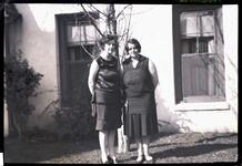 Two Women Standing by Stucco House