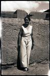 Woman Standing by Adobe Wall
