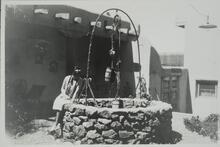 Woman Sitting on a Well near Adobe House