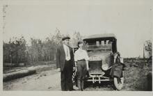 Man and Woman Standing by Old Car