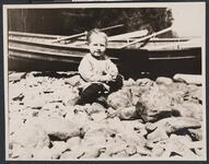 Small Child Seated on Rocks by Boat