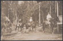 Group on Horseback by Cabin
