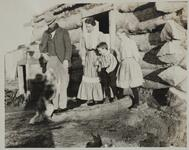 Couple with Two Children and Dog at Cabin Door