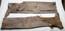 Long leather chaps with two semi-circular pockets and leather fringe attached in six different locations